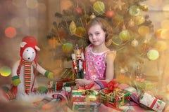 有一个箱子的女孩有在圣诞树附近的一件礼物的 免版税库存图片