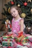 有一个箱子的女孩有在圣诞树附近的一件礼物的 库存照片