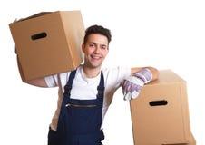 有一个箱子的笑的工作者在他的肩膀 库存图片