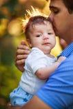 有一个粗野的男婴的他的胳膊的,特写镜头,夏天爸爸 免版税库存照片