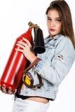 有一个红火灭火器的性感的肉欲的女性消防队员 库存图片