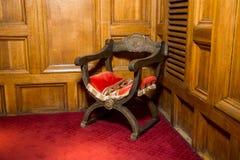 有一个红色位子的一把木古色古香的扶手椅子在隆重的角落 库存照片