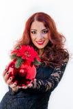 有一个红色圣诞节球的美丽的女孩在她的手上 免版税库存图片