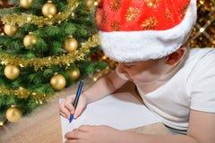 有一个红色圣诞节盖帽的六岁的逗人喜爱的小男孩写信的给圣诞老人在圣诞树附近 聪慧的新年bac 免版税图库摄影