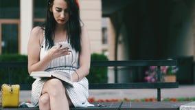 有一个红色外缘的一个俏丽的女孩在她的头坐一条长凳在公园并且读书,然后采取在她的电话 股票录像