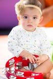 有一个红色小手鼓的女婴 免版税图库摄影