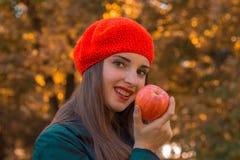 有一个红色帽子的美丽的女孩微笑并且保持苹果计算机手中 库存图片