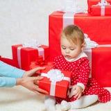 有一个红色当前箱子的可爱宝贝在白色背景 愉快的子项 婴孩礼物 逗人喜爱的小孩举行礼物盒 免版税库存照片