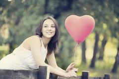 有一个红色形状的心脏气球的愉快的微笑的少妇 免版税库存图片