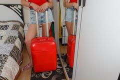 有一个红色手提箱、旅行和休闲的,旅游业少妇 女孩和手提箱 带着旅行手提箱的美丽的女性游人 免版税库存图片