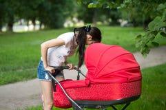 有一个红色支架的母亲在城市公园的步行 免版税库存图片