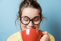 有一个红色杯子的书呆子少妇在蓝色背景 演播室sho 库存照片