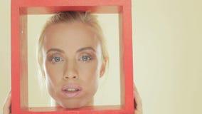 有一个红色框架的白肤金发的妇女 股票录像