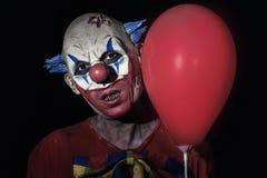 有一个红色气球的可怕邪恶的小丑 免版税库存图片