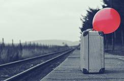 有一个红色气球的老手提箱在与减速火箭的作用的火车站 库存照片