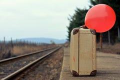 有一个红色气球的老手提箱在与减速火箭的作用的火车站 库存图片
