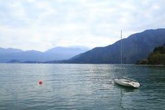 有一个红色浮体的幽静帆船在科莫湖在意大利, 免版税库存照片
