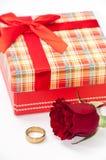 有一个红色玫瑰和金黄圆环的格子花呢披肩箱子 免版税图库摄影