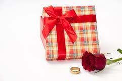 有一个红色玫瑰和金黄圆环的格子花呢披肩箱子 库存照片