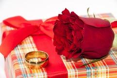有一个红色玫瑰和金黄圆环的格子花呢披肩箱子 图库摄影