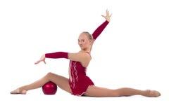 有一个红色球的美丽的女孩体操运动员 库存照片