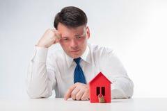 有一个红色纸房子的哀伤的人 免版税图库摄影