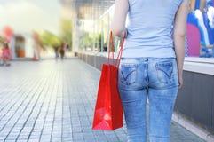 有一个红色袋子的女孩在她的手上在街道上的城市在购物中心旁边 库存照片