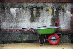 有一个红色轮子和一把红色笤帚的绿色独轮车反对老 库存图片