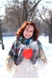 有一个红色重点的浪漫女孩在冬天同水准的背景 免版税库存照片