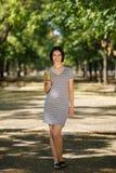 有一个绿色鸡尾酒的惊人的妇女 走在公园背景的素食主义者女孩 素食生活方式概念 复制空间 库存图片