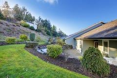 有一个美丽的后院庭院的被镶板的橄榄色的房子 库存图片