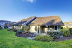 有一个美丽的后院庭院的被镶板的橄榄色的房子 库存照片