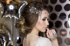 有一个美丽的欢乐的头发新娘的典雅的美丽的女孩新娘与装饰品的一套婚礼礼服的在头,大水晶earr 免版税库存照片
