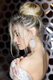 有一个美丽的欢乐的头发新娘的典雅的美丽的女孩新娘与装饰品的一套婚礼礼服的在头,大水晶earr 免版税库存图片