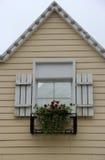 有一个美丽的窗口的三角房子 免版税库存照片
