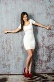 有一个美好的图的女孩在紧身穿戴的超短裙的时髦白色礼服和红色高跟鞋和平台 免版税图库摄影