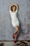 有一个美好的图的女孩在紧身穿戴的超短裙的时髦白色礼服和红色高跟鞋和平台 库存图片