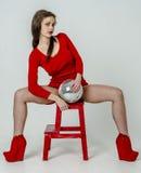 有一个美好的图的女孩在紧身超短裙的一件时髦红色礼服和红色高跟鞋和平台为pa穿戴了 免版税库存图片