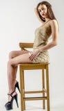 有一个美好的图的女孩在紧身超短裙的时髦金黄礼服和高跟鞋和平台 库存照片