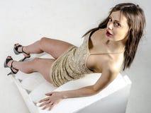 有一个美好的图的女孩在紧身超短裙的时髦金黄礼服和高跟鞋和平台 图库摄影