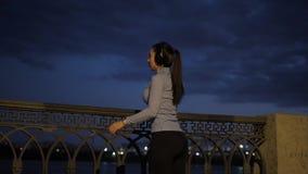 有一个美好的图的女孩运动员沿堤防跑在晚上 女运动员完成锻炼和愉快地 影视素材