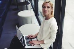 有一个美好的微笑的可爱的学生和短发和坐在与便携式计算机的一个时髦酒吧的一件白色套头衫 库存图片