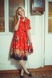 有一个老架线的电话的美丽的白肤金发的妇女在一件红色礼服穿戴了,站立在一个老房子里,葡萄酒样式 库存图片