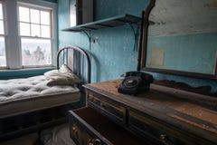 有一个老电话和梳妆台的被放弃的室 免版税库存照片