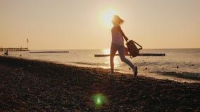 有一个背包和帽子的无忧无虑的妇女在她的手上沿海滨跑在黎明 海滩概念贝壳暑假 影视素材