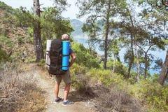 有一个背包的一个游人在供徒步旅行的小道 库存照片