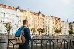 有一个背包的一个游人在老建筑学的背景在布拉格在捷克 他看地图 免版税图库摄影