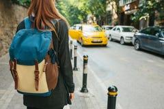 有一个背包的一个年轻旅游女孩在大城市等待出租汽车 旅途 观光 旅行 库存图片
