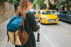 有一个背包的一个年轻旅游女孩在大城市观看在电话的一种流动应用 旅途 观光 库存照片