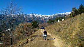 有一个背包的一名妇女在捉住一个小组游人的远足期间 路、树和山的看法 免版税库存照片